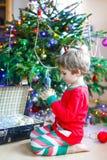 Niño que adorna el árbol de navidad con las bolas Fotos de archivo libres de regalías