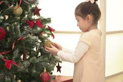 Niño que adorna el árbol de Navidad en sala de estar de la familia Fotos de archivo