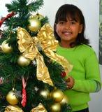 Niño que adorna un árbol de navidad Imagen de archivo