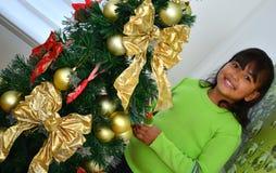 Niño que adorna un árbol de navidad Imagen de archivo libre de regalías
