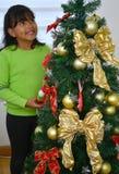Niño que adorna un árbol de navidad Fotos de archivo