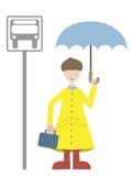 Niño que aguarda el engranaje de la lluvia del omnibus que desgasta Imagen de archivo