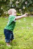 Niño que alcanza para las burbujas de jabón Fotografía de archivo libre de regalías