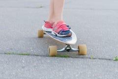 Niño que anda en monopatín en el fondo urbano, piernas del ` s del niño en longboard Imagen de archivo