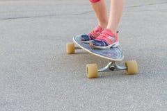 Niño que anda en monopatín en el fondo urbano, piernas del ` s del niño en longboard Fotos de archivo