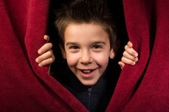 Niño que aparece debajo de la cortina fotos de archivo