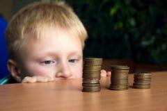 Niño que apila monedas Fotografía de archivo libre de regalías