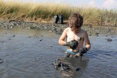 Niño que aplica la arcilla curativa negra Fotografía de archivo libre de regalías