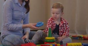 Niño que aprende diversos colores en juegos con la madre almacen de metraje de vídeo