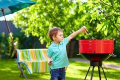 Niño que asa a la parrilla la comida en partido del patio trasero Foto de archivo libre de regalías