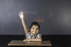 Niño que aumenta la mano en sala de clase. fotos de archivo libres de regalías
