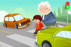 Niño que ayuda a la señora mayor que cruza la calle Fotografía de archivo