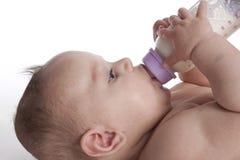 Niño que bebe de la botella de bebé Imágenes de archivo libres de regalías