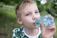 Niño que bebe el agua pura en naturaleza Fotos de archivo libres de regalías