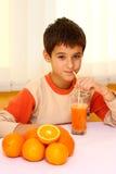 Niño que bebe el zumo de naranja Imágenes de archivo libres de regalías