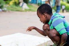 Niño que busca su marca en un mapa Fotografía de archivo