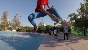 Niño que cae apagado un monopatín en la cámara lenta del cuenco de Skatepark almacen de video