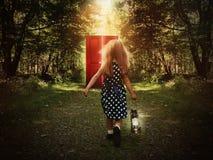 Niño que camina en bosque a la puerta roja que brilla intensamente