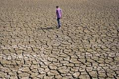 Niño que camina en tierra seca Imagenes de archivo