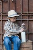 Niño que cierra el casquillo en una botella de leche fresca Foto de archivo