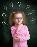 Niño que coloca la pizarra cercana de la escuela con muchos signos de interrogación imagen de archivo libre de regalías