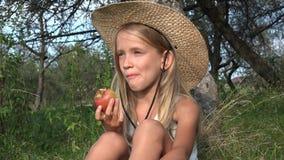 Niño que come Apple en yarda en el pueblo, granjero Girl en la huerta que prueba las frutas 4K