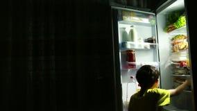 Niño que come delante del refrigerador en medio de la noche almacen de metraje de vídeo