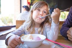 Niño que come el helado del cuenco en restaurante Fotos de archivo