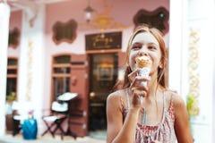 Niño que come el helado en la calle de la ciudad Foto de archivo