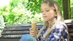 Niño que come el helado en el patio, el sentarse de relajación de la muchacha en banco en el parque 4K metrajes