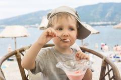 Niño que come el helado en un café en la playa Foto de archivo
