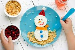Niño que come el muñeco de nieve del requesón Imagenes de archivo