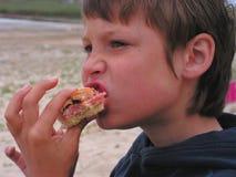 Niño que come el perrito caliente Fotos de archivo