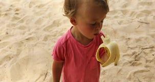 Niño que come el plátano en la playa almacen de video