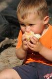 Niño que come el rodillo de pan Imagen de archivo