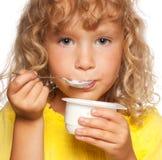 Niño que come el yogur Imagenes de archivo