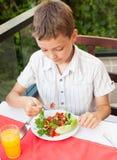 Niño que come la ensalada en un café Fotos de archivo