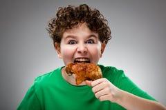 Niño que come la pierna de pollo Fotos de archivo