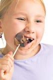 Niño que come la piruleta del chocolate imágenes de archivo libres de regalías