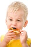 Niño que come la pizza Imagenes de archivo