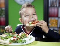 Niño que come la pizza en restaurante foto de archivo