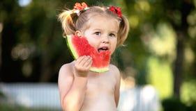 niño que come la sandía en el jardín Los niños comen la fruta al aire libre Bocado sano para los niños Niña que juega en el contr fotografía de archivo libre de regalías