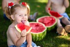 niño que come la sandía en el jardín Los niños comen la fruta al aire libre Bocado sano para los niños Niña que juega en el contr fotos de archivo