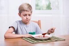 Niño que come la sopa con repugnancia imagen de archivo libre de regalías