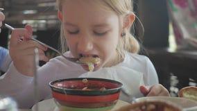 Niño que come la sopa en el café La niña cena Muchacha sonriente hermosa que come la sopa de una placa metrajes