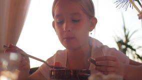 Niño que come la sopa en el café La niña cena Muchacha sonriente hermosa que come la sopa de una placa almacen de metraje de vídeo