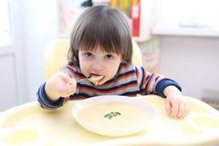 Niño que come la sopa poner crema vegetal Foto de archivo