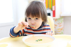 Niño que come la sopa poner crema vegetal Nutrición sana Imagenes de archivo