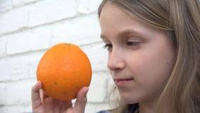 Niño que come las frutas de las naranjas en el desayuno, niño de la muchacha que huele la cocina sana de la comida