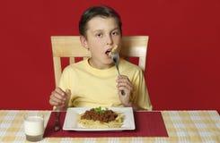 Niño que come las pastas Fotos de archivo